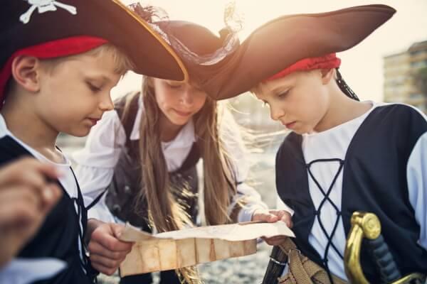 Kinder in Piratenkostümen mit Schatzkarte