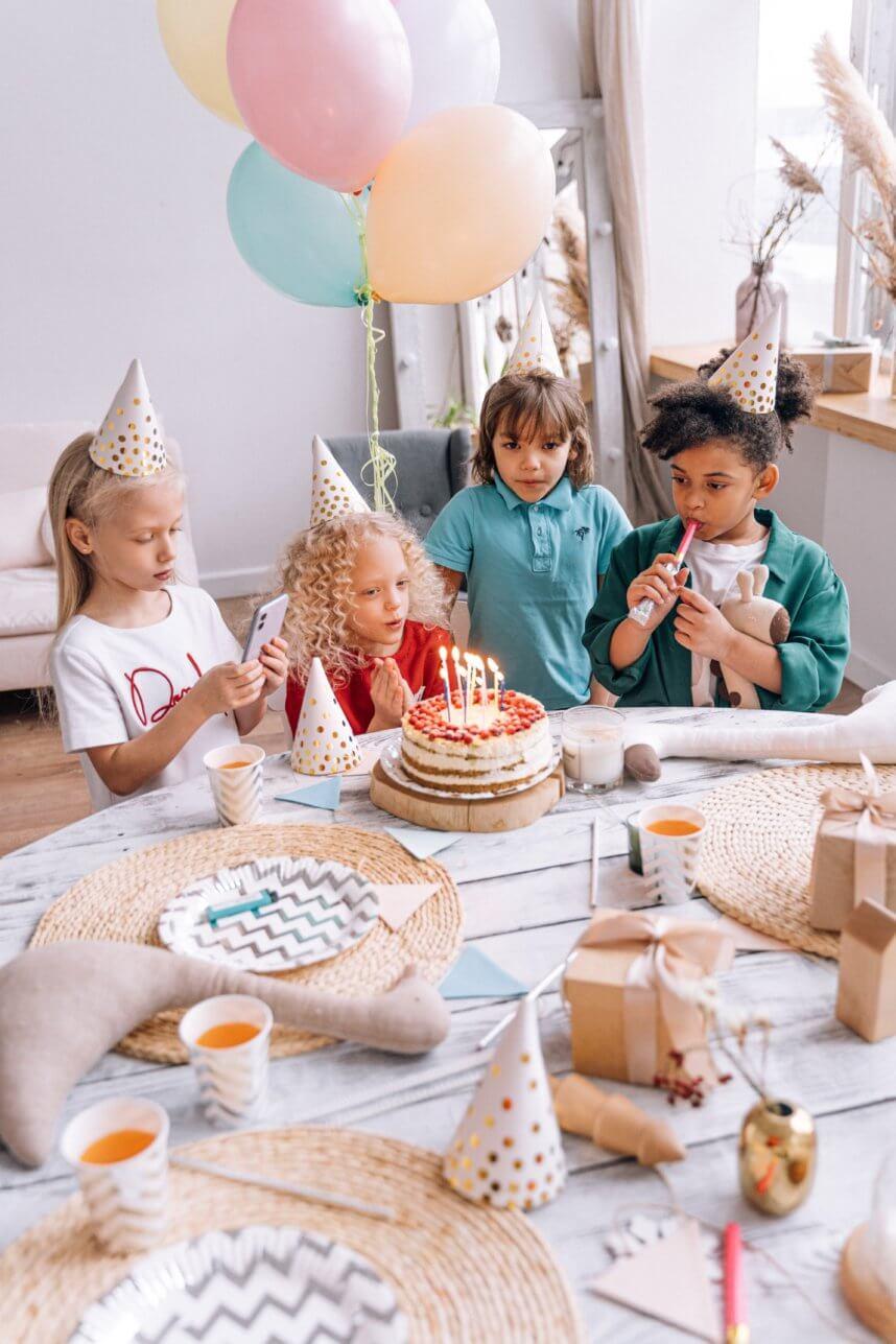 Kinder sitzen am Geburtstag vor Torte
