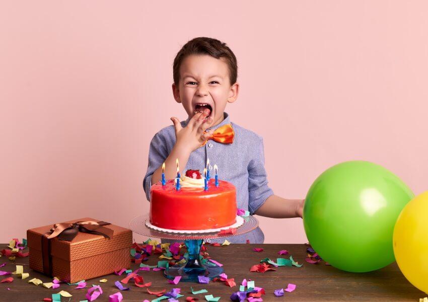 Junge mit Torte und Ballons